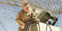 Soldier preforms preventative checks and maintenance on a satellite communication system.
