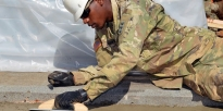 U.S. Army Soldiers shovel aggregate