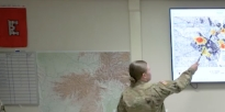 Soldier identifies a location on a map.