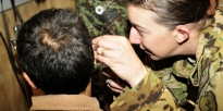 Soldier shows a technique to check the ear drums of a patient while conducting a physical after a hearing test.