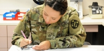 Soldier filling out paperwork.