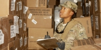 U.S. Army Soldier inspects pallets of food
