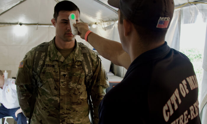 A soldier gets his temperature taken.