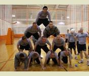 Army ROTC members build a human pyramid to cheer on their fellow cadets competing in a volleyball game during the annual Army and Air Force week long competition.