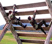 Cadets skillfully negotiate an obstacle during a field training exercise.
