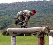 Cadet skillfully leaps over a log while negotiaing the obstacle course.