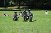 Cadets plan an attack against the opposing force (OPFOR) during a game of paintball.