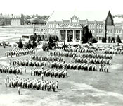 Corps of cadets participating in drill and ceremony through stationary and moving techniques in front of Armory/Gymnasium that once housed ROTC that had a maximum enrollment of over four thousand cadets. The building now houses the School of Architecture.