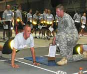 CDT CPT Justin Selking performing the two minute push-up event while an Indiana National Guardsmen grades him to standard