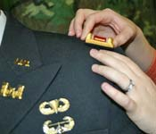 An Army ROTC Cadet gets his 2LT Rank pinned on by his wife during the End of Semester Commissioning Ceremony