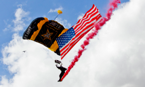 Golden Knight team member delivers the U.S. flag during a jump
