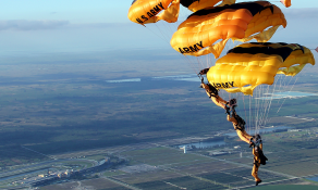 Golden Knights team members stack multiple parachutes during a jump