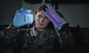 Soldier holding a black light and a jar.