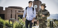 Male ROTC Cadet wearing civilian clothing and a backpack with a female wearing OCP holding books walking up steps outside during the daytime.