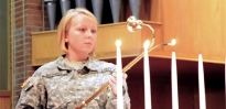 A chaplain assistant lights candles before a religious service