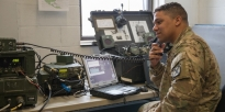 Soldier does a voice and data radio check using high frequency radio equipment.