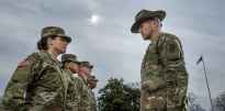 U.S. Army Drill Sergeant inspecting soldiers in a formation.